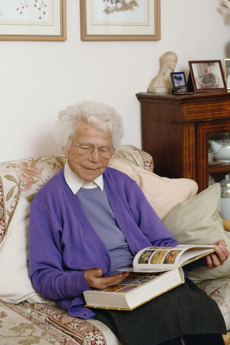 Picture of elderly lady sitting on  a settee  looking through a gardening book