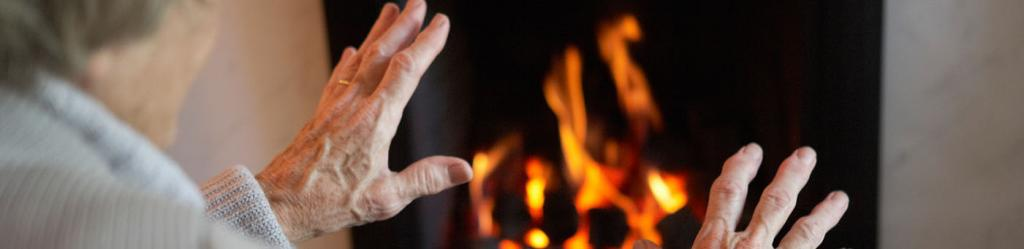Picture of an old lady warming her hands by the fireside